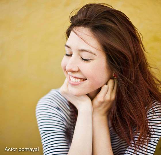 Woman resting her face on her hands, smiling