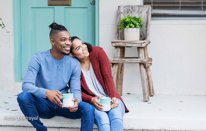 Couple sitting on front steps drinking coffee