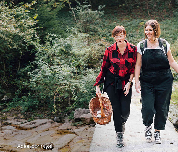 Two women walking on a trail in the woods