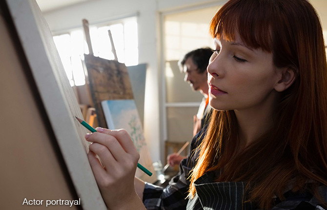Woman sketching on a canvas at an art class