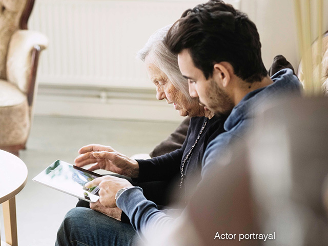 Young man and older woman looking at a tablet
