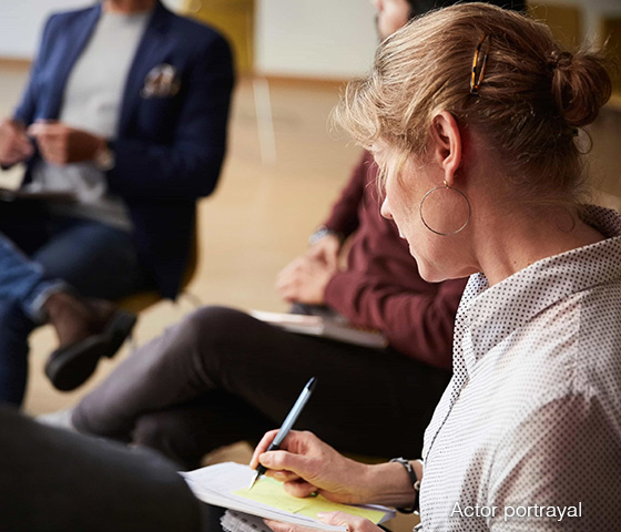 A woman sitting in a group taking notes