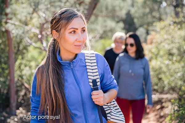 Three women hiking through the woods