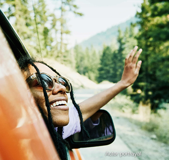 Woman smiling as she sticks her head out the window of a car