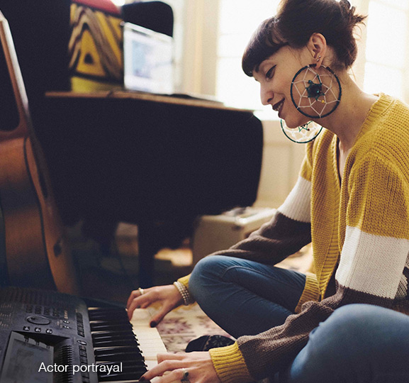 Woman sitting on the floor playing keyboard
