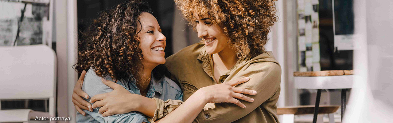 Two women smiling and embracing